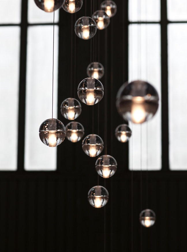 A linear cluster of 14.1 Pendant Lights hanging in a dimly lit space.